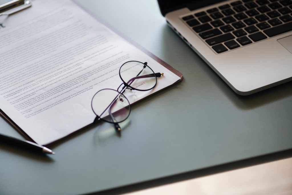 Photo of forms, glasses, and laptop (credit to rawpixel from Unsplash)